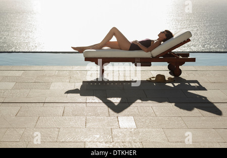 Woman sunbathing in lounge chair at poolside overlooking ocean - Stock Photo