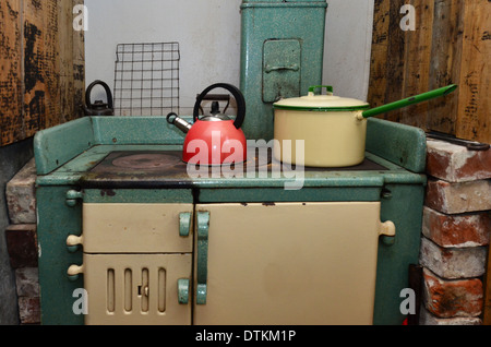 An old stove with cookeries in vintage kitchen. - Stock Photo