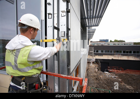 Workman on a cherry picker securing insulation cladding and paneling at Swansea university in South Wales UK. - Stock Photo