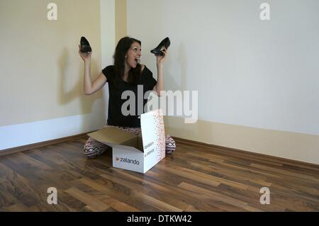 Berlin, Germany. 12th July, 2013. ILLUSTRATION - A woman sits in front of a shoebox of multinational e-commerce - Stock Photo