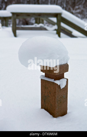 Snow piled up on top of a wooden post - Stock Photo