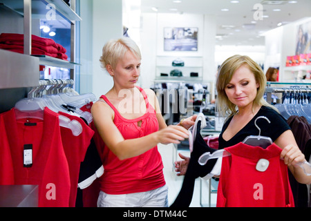 Two women looking and comparing different clothes in shop. Retail store, fashion. - Stock Photo