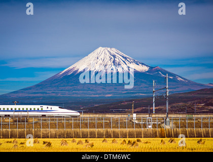 Mt. Fuji in Japan with a train passing below. - Stock Photo