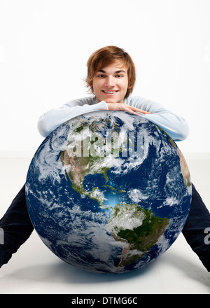 Young man resting over a small planet earth - Stock Photo