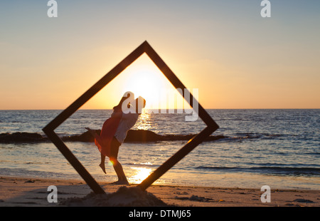 couple kiss and hug at the beach behind a frame on the sand during ...