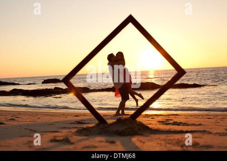 couple kiss and hug behind a frame on the beach Stock Photo ...