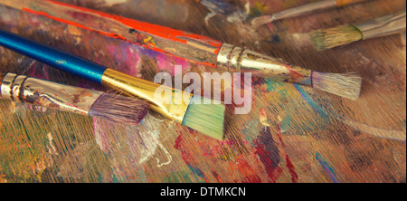 A small collection of artists brushes on a wooden palette - Stock Photo