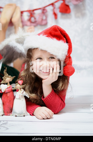 Smiling and cute girl in a Santa hat - Stock Photo