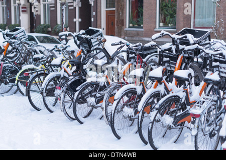 A row of bikes in Amsterdam, covered in snow. - Stock Photo
