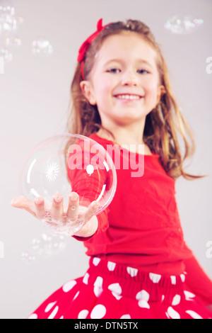Little woman making large soap bubbles - Stock Photo