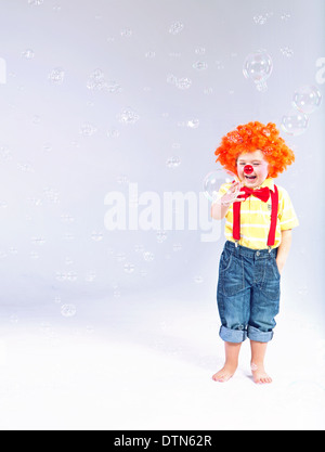 Funny picture of little clown making large soap bubbles - Stock Photo