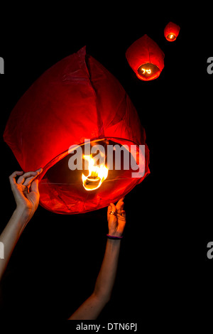 Launching sky lanterns in the night - Stock Photo