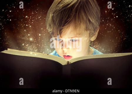 Little boy and the old magic book - Stock Photo