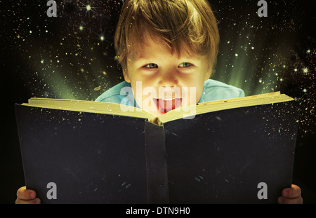 Small boy carrying an old magic book - Stock Photo