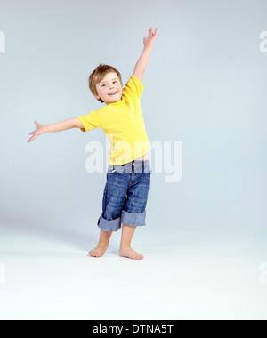 Joyful little man playing a plane - Stock Photo