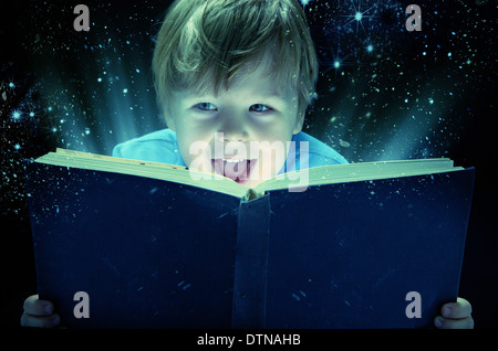 Laughing small boy with the old magic book - Stock Photo