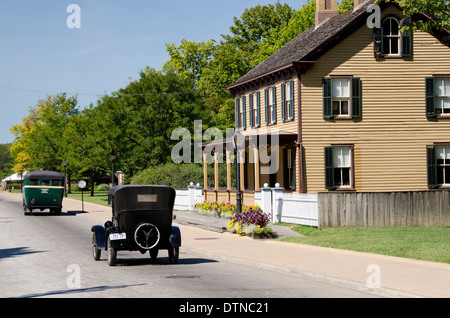 Michigan, Dearborn. Greenfield Village, National Historic Landmark. Vintage cars in front of historic home. - Stock Photo