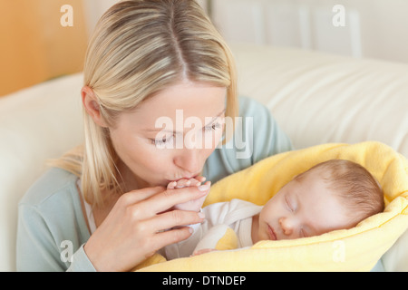 Mother on the sofa kissing her baby's hand - Stock Photo