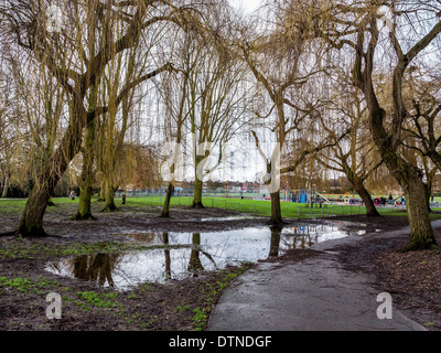 Crane Park - muddy puddles and standing water after heavy winter rainfall near Children's playground - Twickenham, - Stock Photo