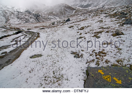 Yellow painted sign on rock of the Alta Via no. 2 mountain trail in snow covered mountains, Gran Paradiso National - Stock Photo