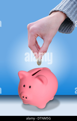 Female hand putting a coin euro in a piggy bank - Stock Photo