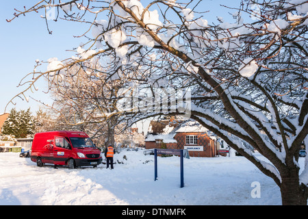 Parcel Force van being dug out of an icy road by drivers after getting stuck in difficult driving conditions. - Stock Photo