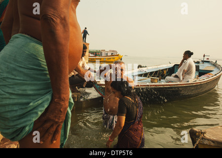 A couple bathing in the ganges, Varanasi, India - Stock Photo