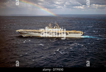 US Navy forward-deployed amphibious assault ship USS Bonhomme Richard steams through the East China Sea past a rainbow - Stock Photo