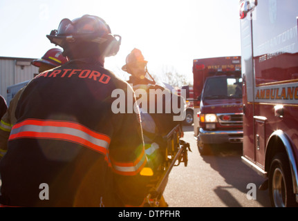 A Hartford firefighter pulling a stretcher with a victim to an ambulance - Stock Photo