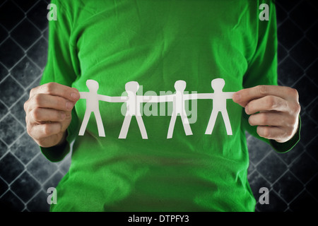 Man holding chain of people paper cuts, teamwork concept. - Stock Photo