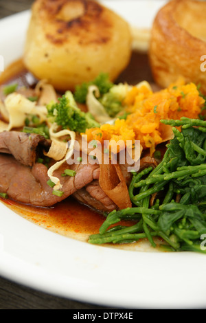 Roast beef dinner with roast potatoes, Yorkshire pudding and vegetables mashed swede and samphire - Stock Photo