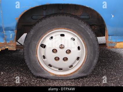 Flat tire on rusty blue van parked on asphalt - Stock Photo