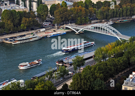 View of the embankment of the Seine river with boats and arched pedestrian bridge from the observation deck of the - Stock Photo