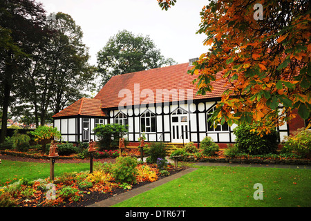 A mock-Tudor half-timbered church with a red tile roof in autumn. - Stock Photo