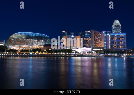 An electric, night view of the Esplanade, as seen from Merlion Park and the mouth of the Singapore River in Singapore. - Stock Photo