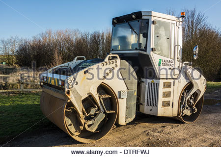 Lafarge Tarmac road roller used in the construction of roads, parked in a layby in the early morning sun. - Stock Photo