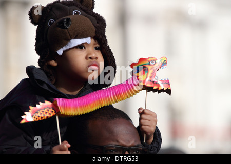 Child celebrates Chines new year in London's Trafalgar square wearing traditional Chinese dress. - Stock Photo