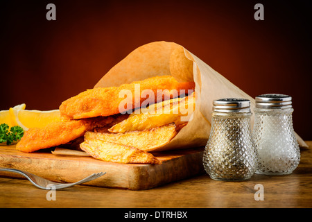 traditioanl fish and chips meal wrapped in paper - Stock Photo