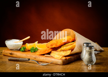 delicious traditional fish and chips meal with lemons and dip - Stock Photo