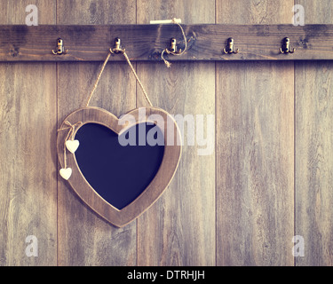 Heart shape menu board hanging on wooden panel wall - vintage tone effect added to wood - Stock Photo