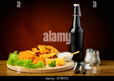 still life with traditional fish and chips meal on a wooden plate - Stock Photo