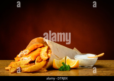 still life with traditional fish and chips menu, lemons and dip sauce - Stock Photo