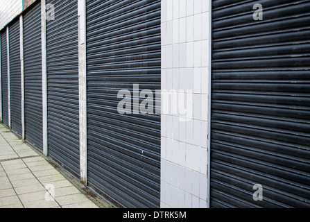 Detail of closed metal shutters on a shop front in the UK highlighting the impact of recession and economic downturn - Stock Photo
