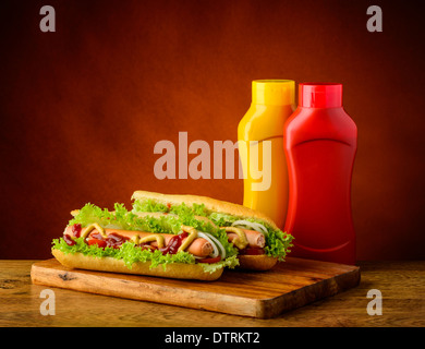 still life with two hotdogs, mustard and ketchup - Stock Photo