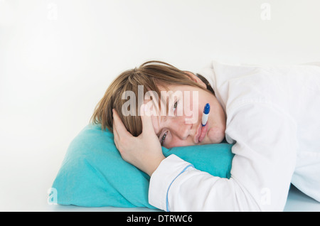 Sick girl with thermometer in her mouth laying on a pillow. - Stock Photo