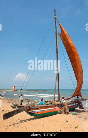 Fisherman with traditional outrigger sailing canoe known as Oruvas on the Negombo beach. Western Province, Sri Lanka. - Stock Photo