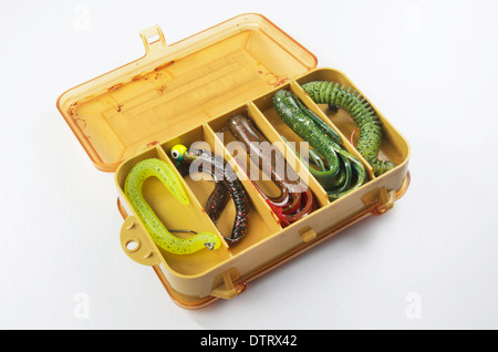Bass bait, or old fishing tackle box with rubber worms and tubes. - Stock Photo