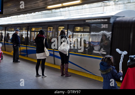 Passengers waiting for the Skytrain commuter train as it arrives into the station in downtown Vancouver, BC Canada. - Stock Photo