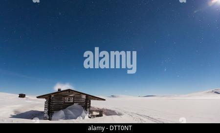 Pitsusjärvi wilderness hut at night time during full moon, Enontekiö, Lapland, Finland, EU - Stock Photo