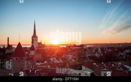 Morning cityscape with rising sun in old town of Tallinn, Estonia - Stock Photo